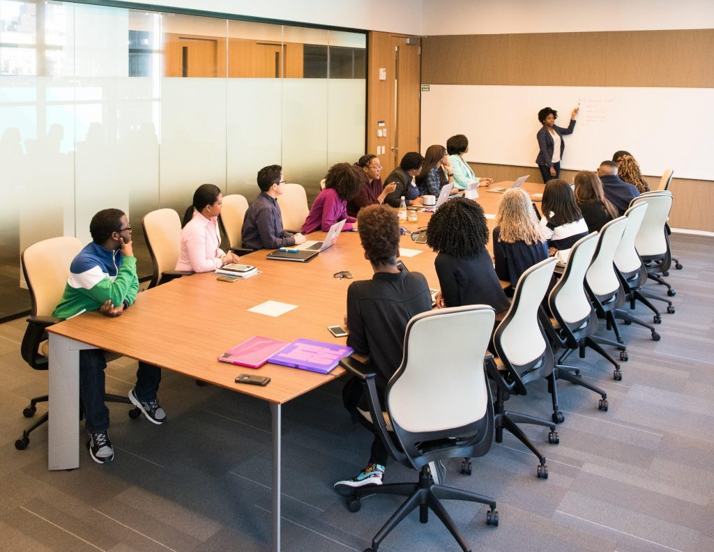 Lady presenting on a whiteboard to a group of young people